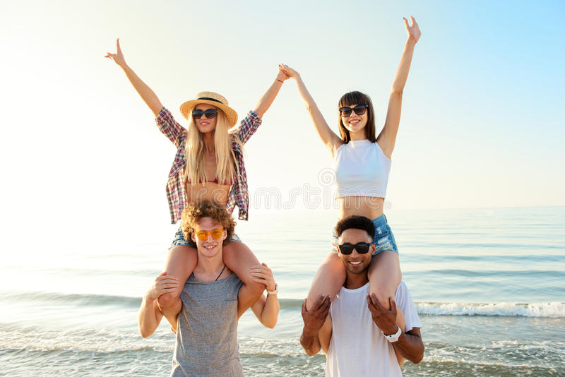 Happy smiling couples playing at the beach stock photo