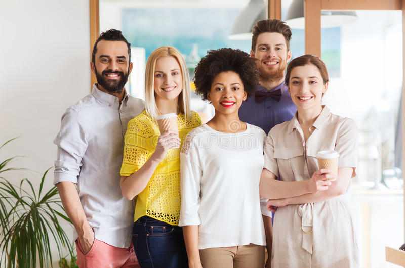 Happy smiling creative team with coffee in office stock image