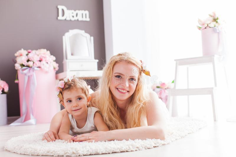 Happy smiling daughter and mom laying on a floor in their house stock image