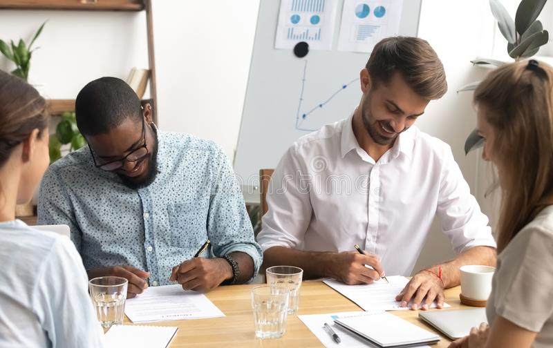 Happy smiling diverse businessmen putting signature on paper document stock photos