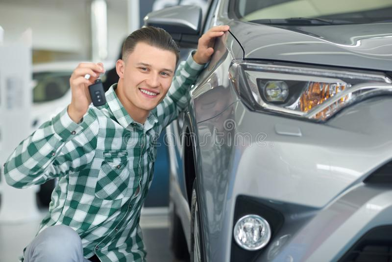 Happy smiling driver buying grey vehicle and showing key. royalty free stock images