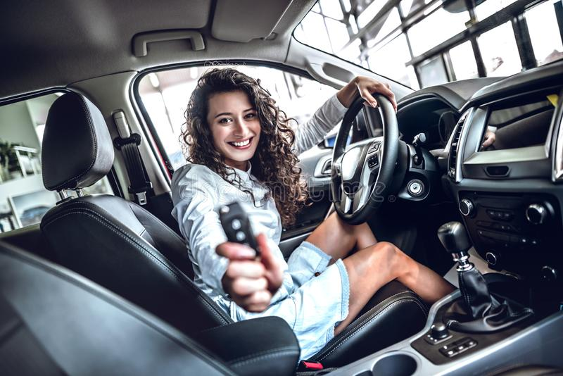 Happy smiling driver woman showing car key sitting in new auto stock images