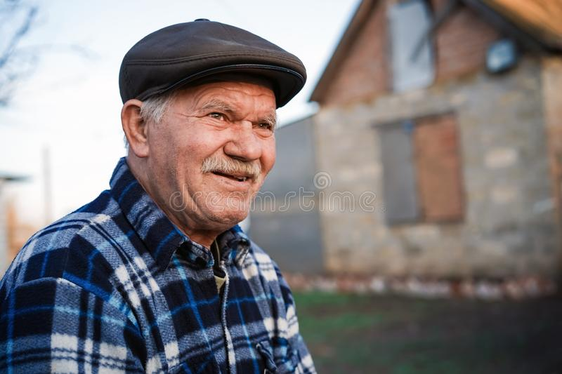 Happy smiling elder senior man portrait with a mustache in a cap on the background of a brick house in a Russian village royalty free stock photography