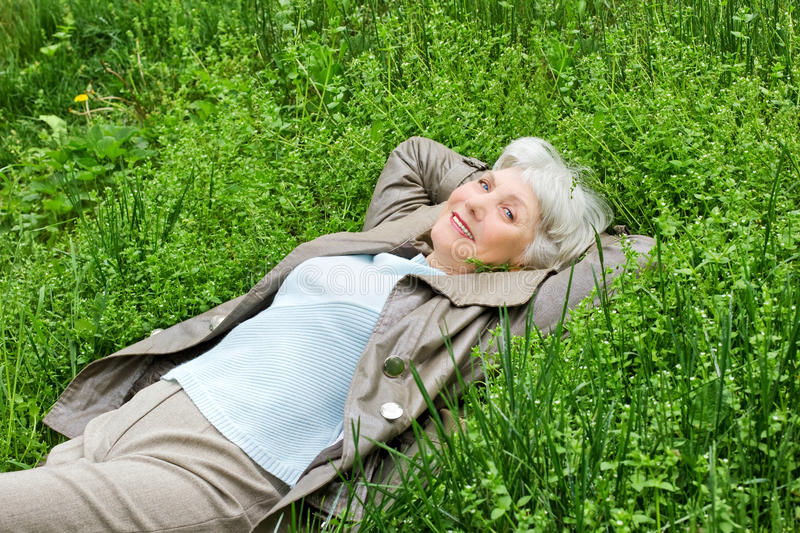 Happy smiling elderly woman lying on green grass meadow in spring stock image