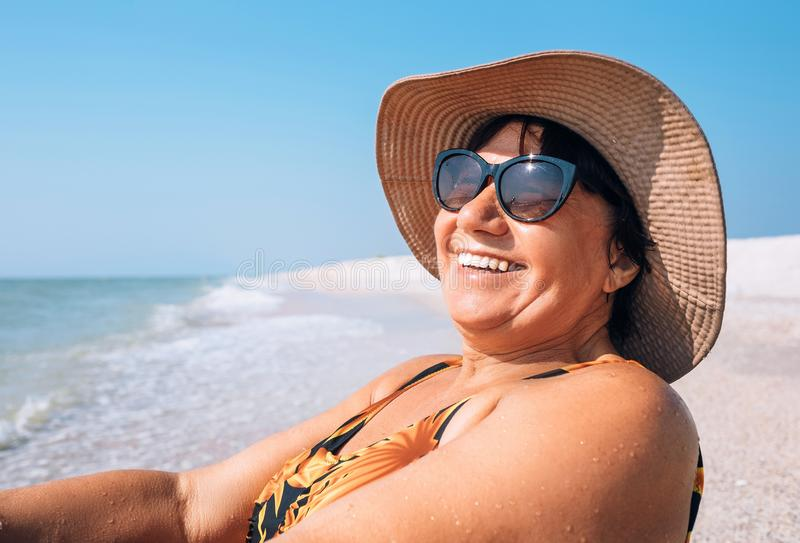 Happy smiling Elderly womanr woman in sunglasses and big hat takes sun bath on seaside stock images