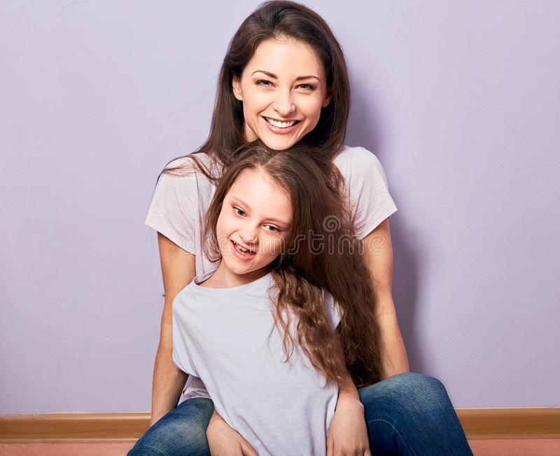 Happy smiling emotion mother cuddling her cute daughter sitting on the floor with love on purple background with empty copy space stock images