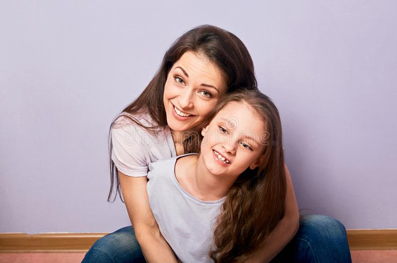 Happy smiling emotion mother cuddling her cute daughter sitting on the floor with love on purple background with empty copy space stock image