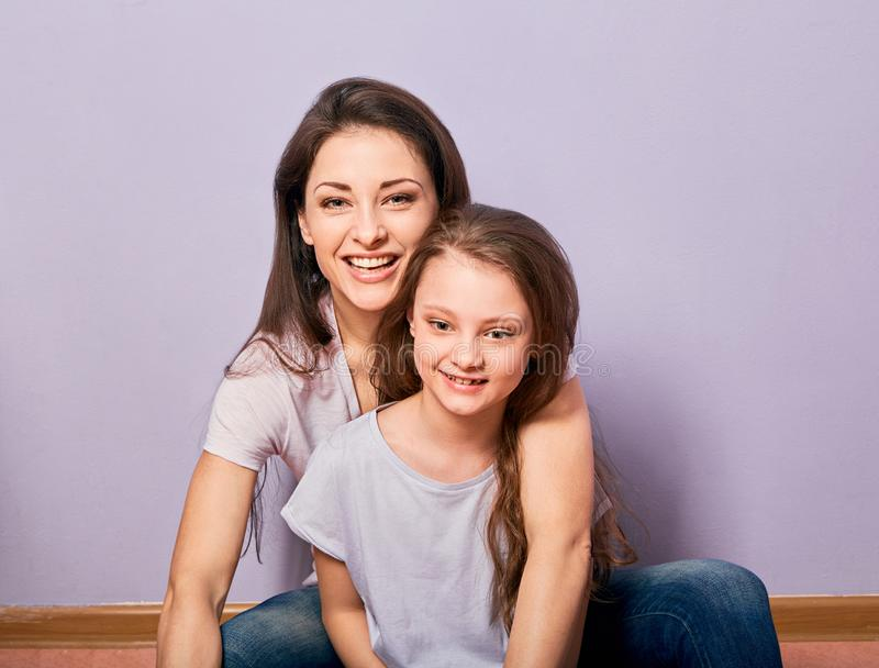 Happy smiling emotion mother cuddling her cute daughter sitting on the floor with love on purple background with empty copy space royalty free stock photography