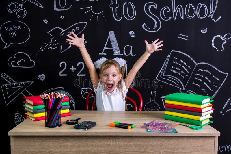 Happy, smiling and excited schoolgirl sitting at the desk with both arms up, surrounded with school supplies. Chalkboard stock image