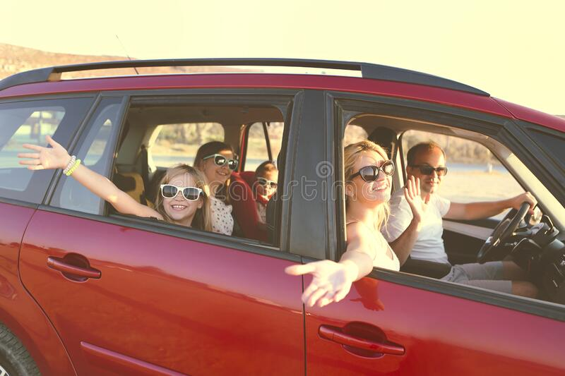 Happy smiling family with daughters in the car with sea background royalty free stock images