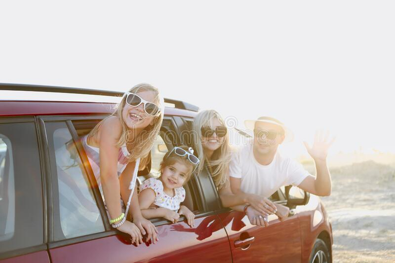 Happy smiling family with daughters in the car with sea background royalty free stock photo