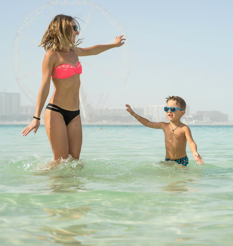 Happy smiling family having fun on tropical white beach Maldives islands. Mother and cute son. Positive human emotions, feelings royalty free stock image