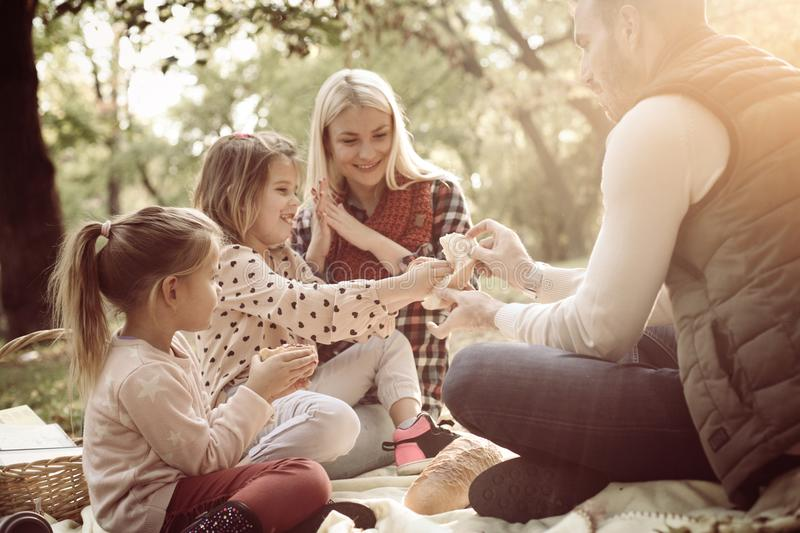 Smiling family having picnic together in park and talking. royalty free stock image