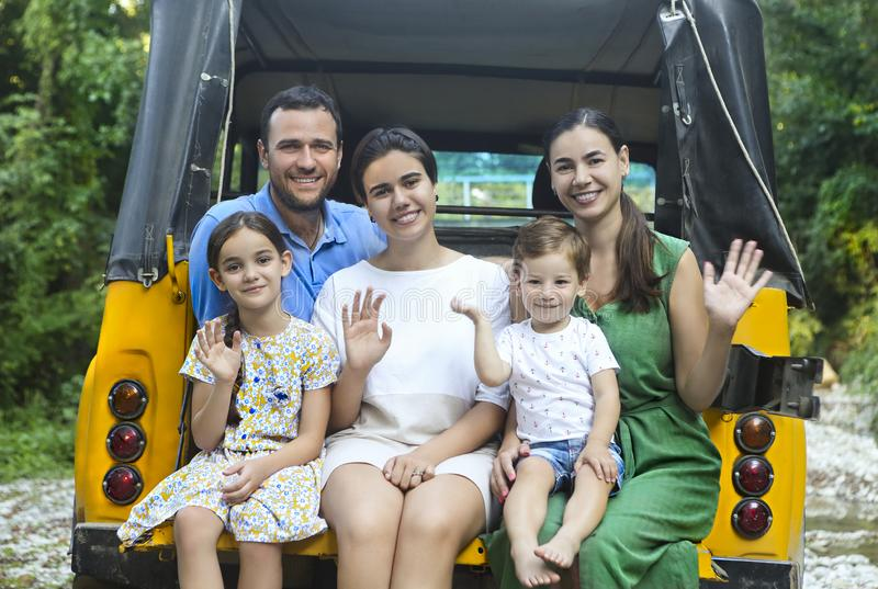 Happy smiling family with kids in the car with mountain river background royalty free stock photos