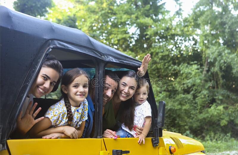 Happy smiling family with kids in the car with mountain river background stock image