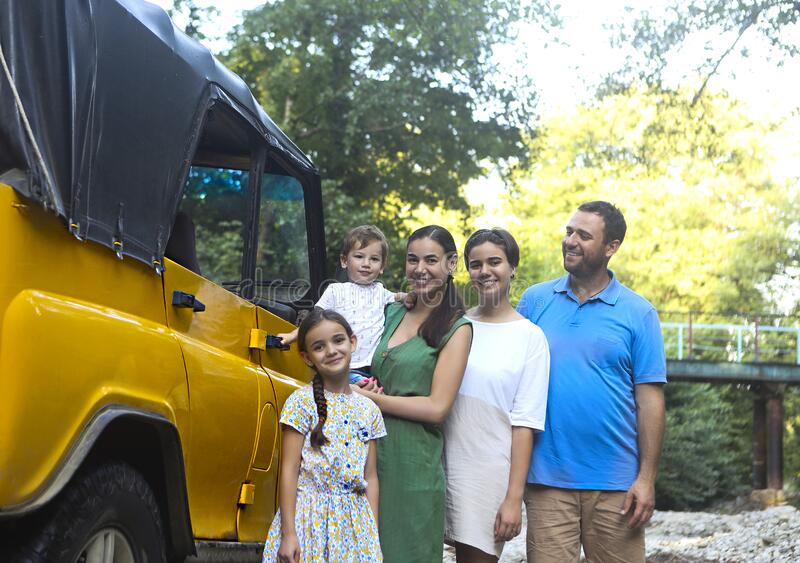 Happy smiling family with kids by the car with mountain river background royalty free stock photo