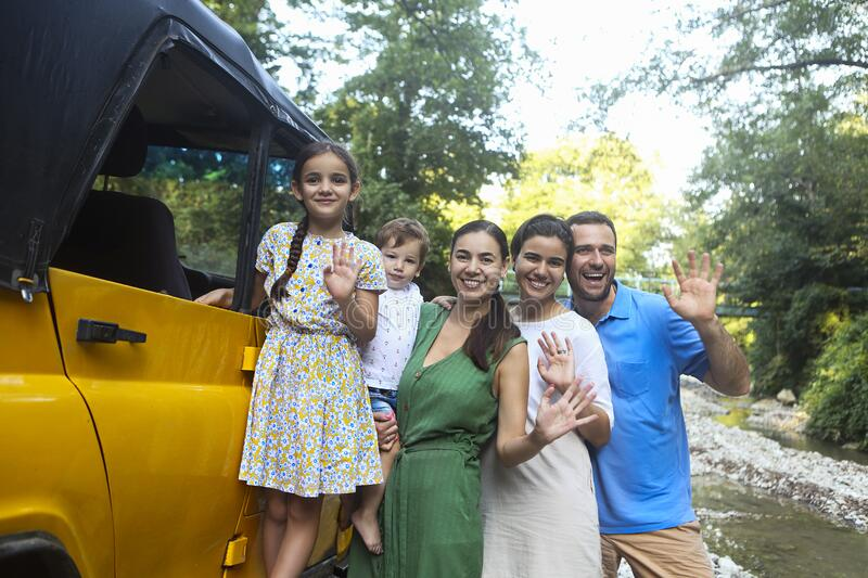 Happy smiling family with kids by the car with mountain river background. Portrait of a smiling family with children in country stock images