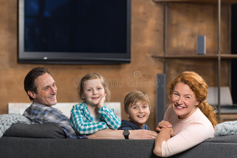 Happy Smiling Family Sitting On Couch In Living Room, Parents Couple With Two Children. At Home stock images