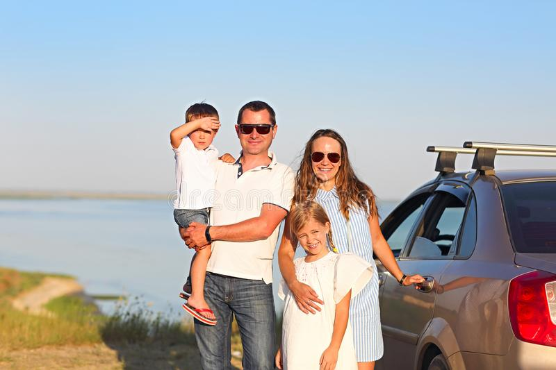 Happy smiling family with two kids by the car with sea background. Portrait of a smiling family with two children at beach by stock image