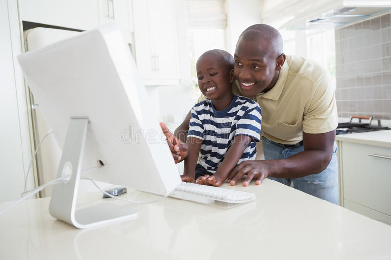 Happy smiling father with his son using computer. In the kitchen stock photo