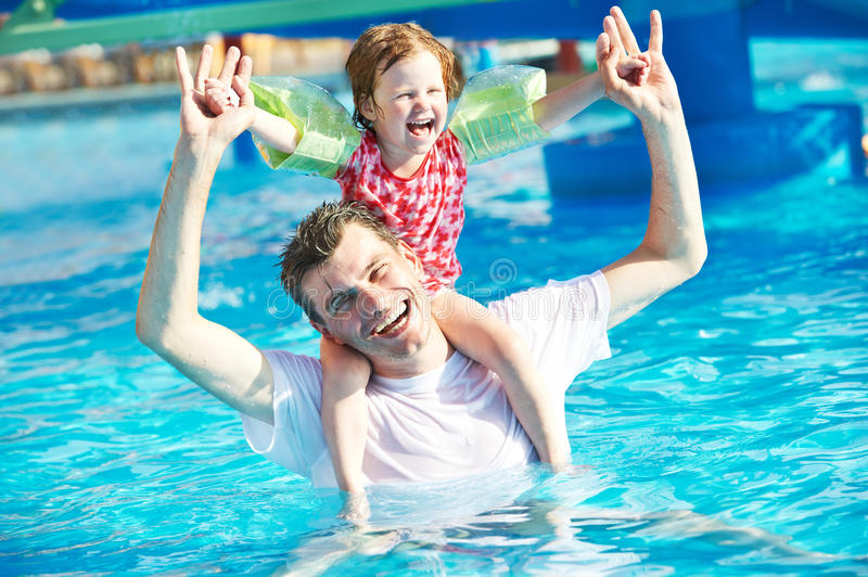 Father and child in resort swimming pool royalty free stock photo