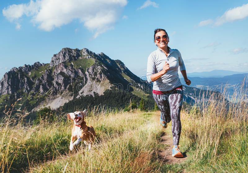 Happy smiling female jogging by the mounting range path with her beagle dog. Canicross running healthy lifestyle concept image royalty free stock photos