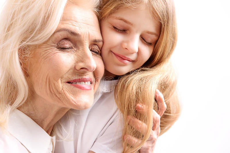 Happy smiling female persons necking. Cheerful grandmother is hugging her grandchild with closed eyes. They are brightly smiling stock photography