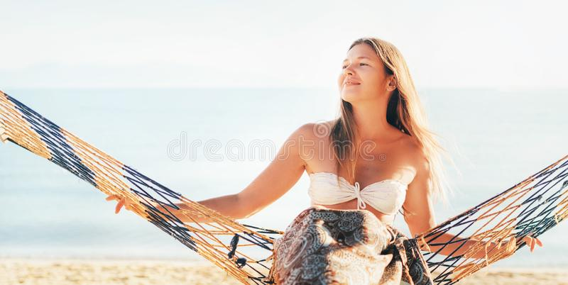 Happy smiling female swinging in hammock hinged between palm trees at the sea side stock image