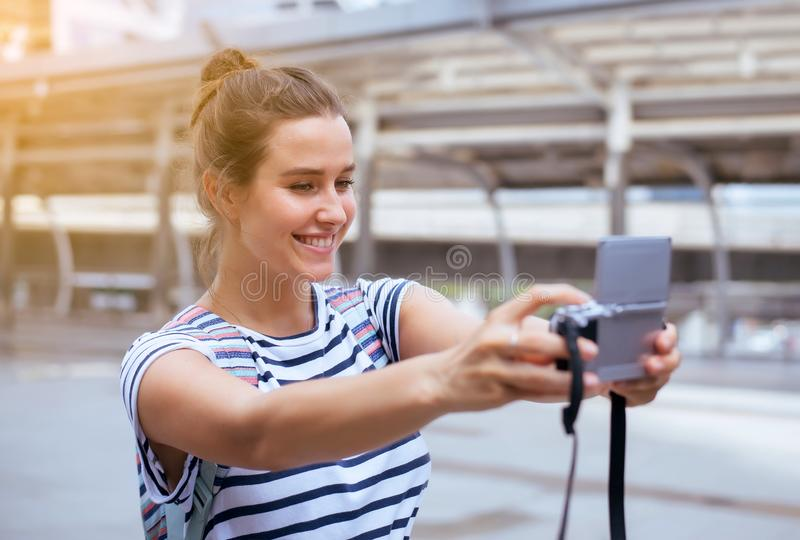 Happy and smiling female traveler is making her selfie in the city,Beautiful girl walking on the streets. Happy and smiling face female traveler is making her stock photo