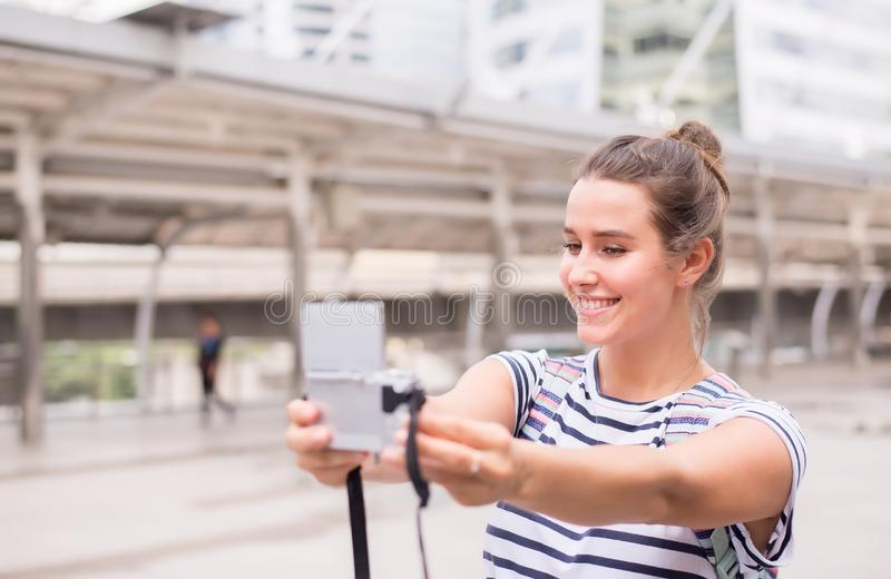 Happy and smiling female traveler is making her selfie in the city,Beautiful girl walking on the streets. In vacations stock photo