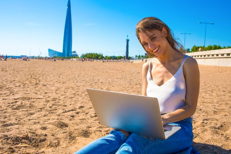 Happy smiling female university student using netbook for online education royalty free stock images