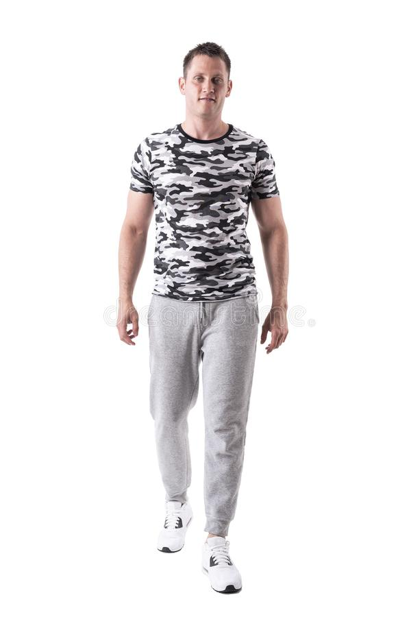 Happy smiling fit man in sport sweatpants and army shirt walking and looking at camera. stock photo