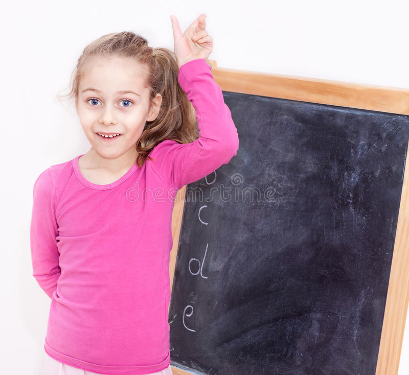 Happy smiling five years old child girl in front of blackboard. Happy smiling five years old caucasian blond child girl in front of blackboard on white stock image