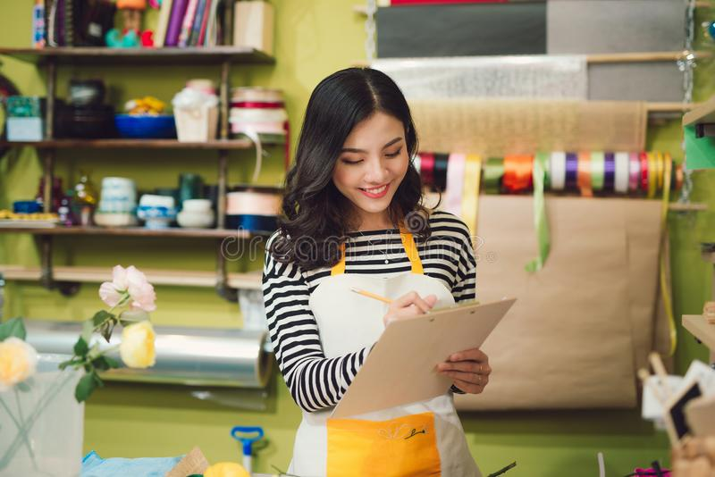 Happy smiling florist woman with tablet pc computer at flower sh stock image