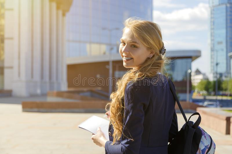 Happy smiling freelance student walking on city street. Woman in casual clothes and backpack looking backward. Skyscrapers and. Campus landscape. Artist making royalty free stock photo