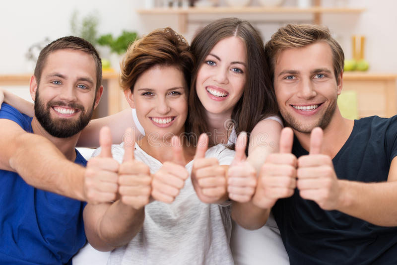 Happy smiling friends giving a thumbs up stock photo