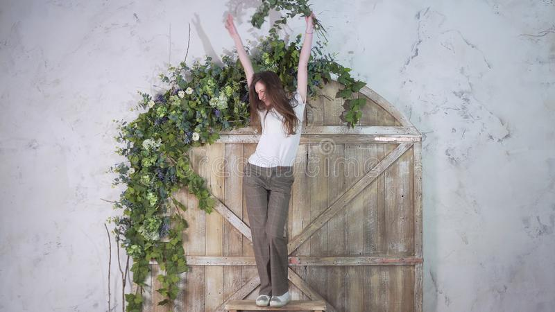 Happy smiling girl dancing on a stepladder on the background of a beautiful wooden gate decorated with flowers royalty free stock images