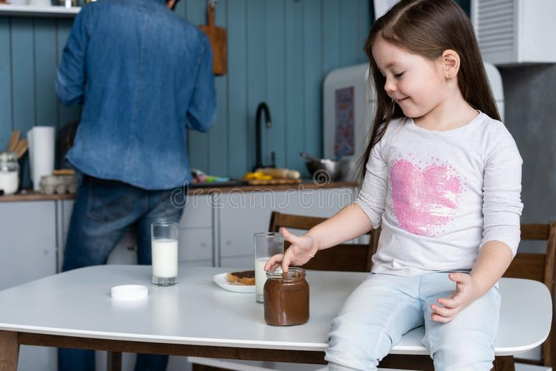 Happy smiling girl eating sandwich for breakfast and looking at the camera in the kitchen stock images