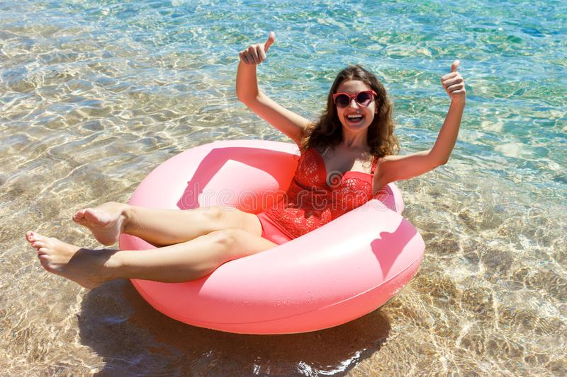 Happy Smiling girl enjoys floating on inflatable donut in sea. vacation time.  stock photos