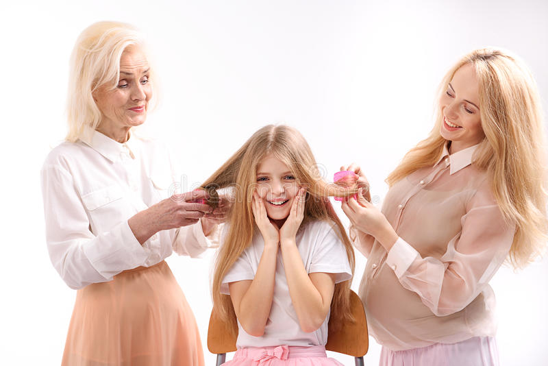 Happy smiling girl among family. Connection between generations. Hilarious women are doing hairstyle for daughter. . Portrait stock image