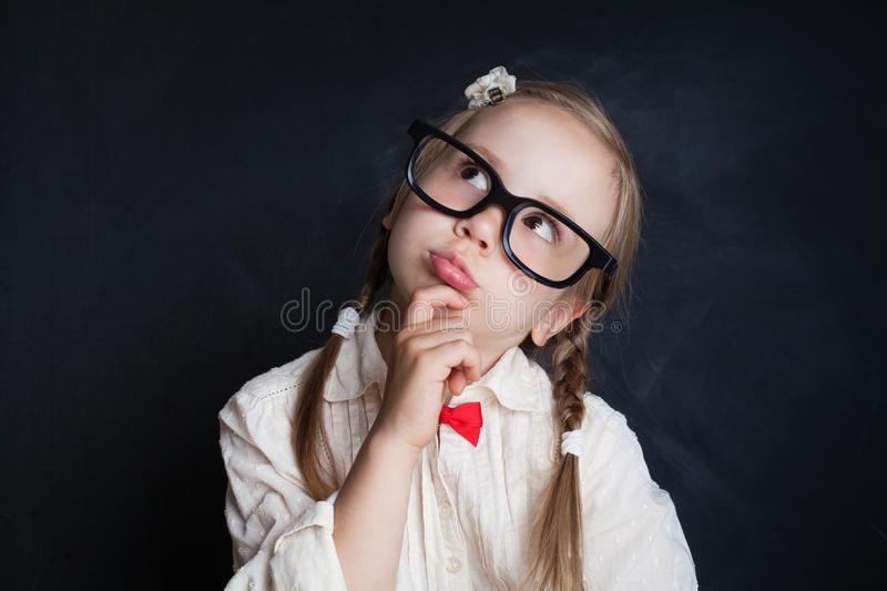 Happy smiling girl in glasses thinking and looking up royalty free stock photo