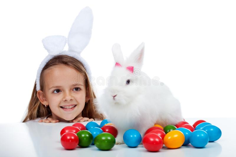 Happy smiling girl with her newly found easter rabbit and colorful eggs on a table stock image