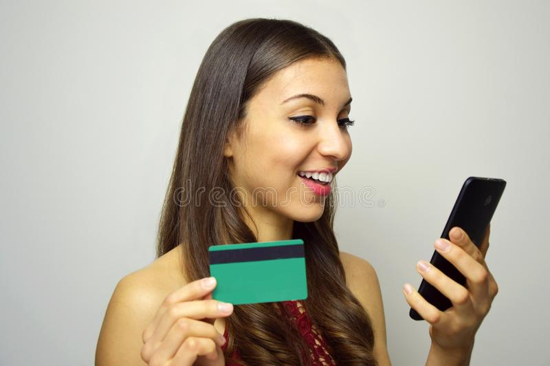 Happy smiling girl holding and looking to her smart phone with credit card in other hand on white background. E-commerce woman. Pe stock photos