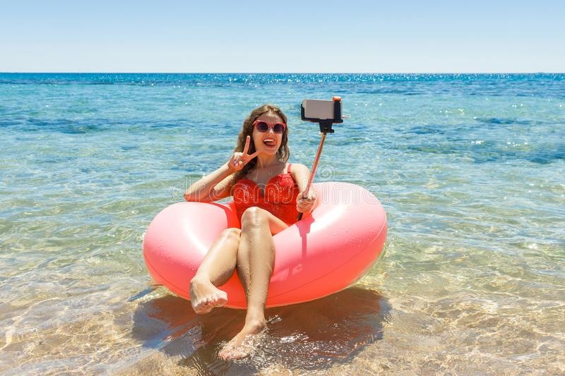 Happy Smiling girl makes selfie floating on inflatable donut in sea. vacation time.  royalty free stock images
