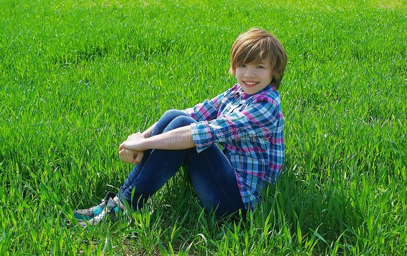 A happy, smiling girl sits on the green grass on a bright Sunny day sideways and hugs her legs. stock photography
