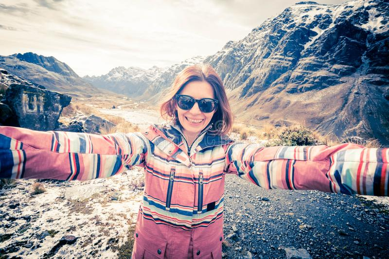 Happy smiling girl taking selfie in rocky Andes stock photo