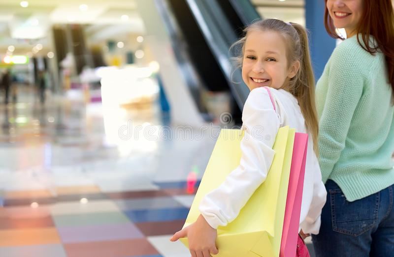 Happy smiling girl walking along the shopping mall with her mother and shopping bags stock image