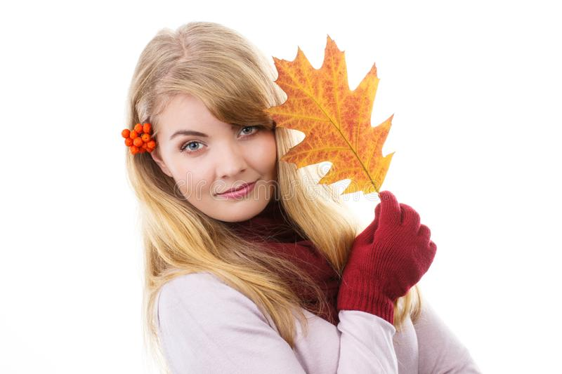 Happy smiling girl in woolen gloves holding autumnal leaf royalty free stock image