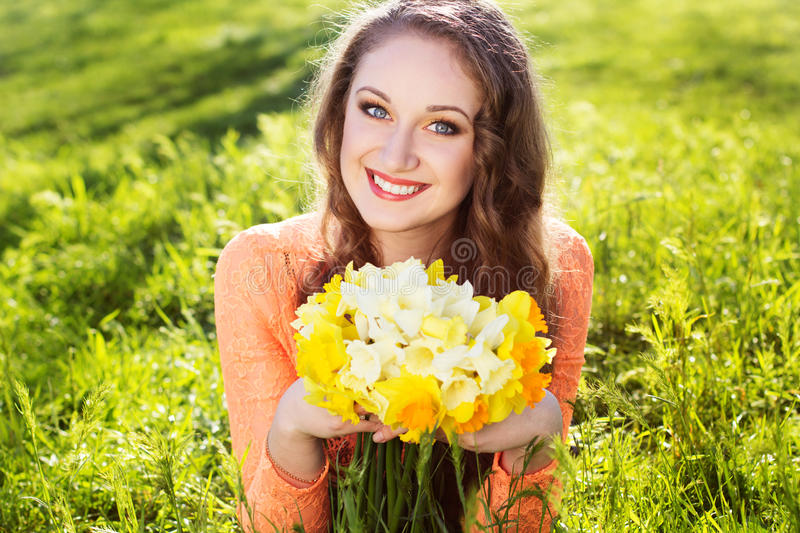 Happy smiling girl with yellow flowers stock photography