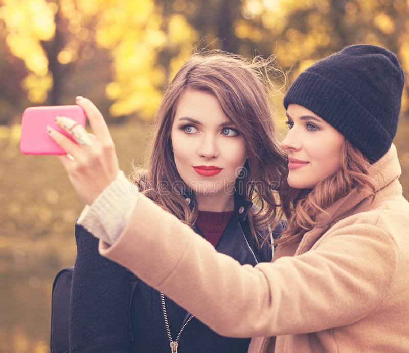 Happy Smiling Girls with Cell Phone Taking Selfie in Autumn Park. Fashion Model with Smartphone stock photo